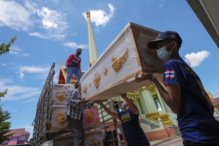 People donate an empty coffin for the Wat Ratprakongtham temple Nonthaburi Province, Thailand, Monday, July 12, 2021. Wat Ratprakongtham temple offering free funeral service for people dying from COVID-19 says it is struggling to keep up with 24-hour cremation, and is adding another crematorium as Thailand sees a growing number of cases and deaths in a coronavirus surge that began in early April. (AP Photo/Sakchai Lalit)
