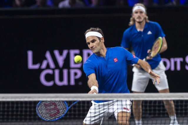Team Europe's Stefanos Tsitsipas, rear, and teammate Roger Federer, front, play against Team World's John Isner and Jack Sock during a men's doubles tennis match at the Laver Cup tennis event in Geneva, Sunday, Sept. 22, 2019. (Martial Trezzini/Keystone via AP)