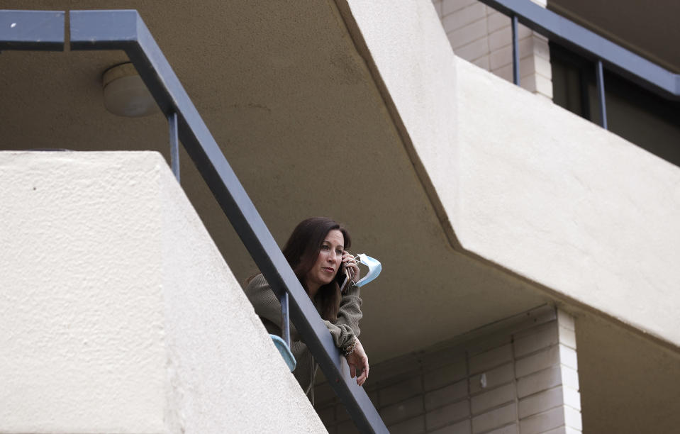 U.S. citizen Michelle Parker talks on her phone as she poses for a photo on the balcony at her home in Sydney on Oct. 20, 2020. Parker is a flight attendant and Australia considers her an essential worker who flies between her Sydney home and San Francisco. But New South Wales state's added layer of strict quarantine rules meant that when she was returning to her husband and children in Sydney for days, she was no longer considered an essential worker but a traveler who was expected to pay 3,000 Australian dollars ($2,100) to quarantine in a Sydney hotel for two weeks. (AP Photo/Rick Rycroft)