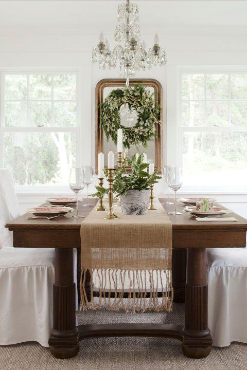 """<p>A neutral tablecloth and slipcovers lighten up the heavy oak dining-room set. A wreath is turned into a framed work of art by hanging it atop a mirror.</p><p><a href=""""https://www.amazon.com/Burlap-Runner-Fringed-inches-Natural/dp/B00J8AOU40"""" rel=""""nofollow noopener"""" target=""""_blank"""" data-ylk=""""slk:SHOP BURLAP RUNNERS"""" class=""""link rapid-noclick-resp"""">SHOP BURLAP RUNNERS</a></p>"""