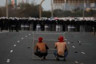 FILE PHOTO: Anti-government protesters take cover in front of riot police blocking the road leading to Pearl Square in Manama