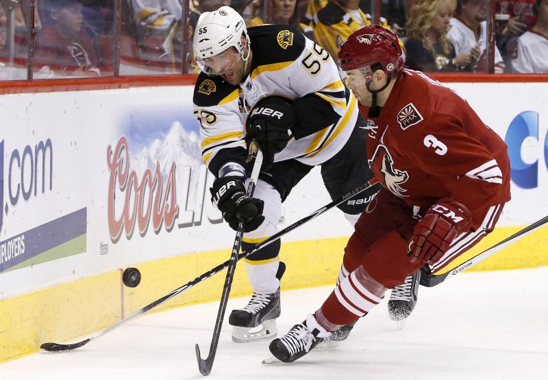 Boston Bruins' Johnny Boychuk (55) and Phoenix Coyotes' Keith Yandle (3) battle for the puck during the first period of an NHL hockey game on Saturday, March 22, 2014, in Glendale, Ariz. (AP Photo/Ross D. Franklin)