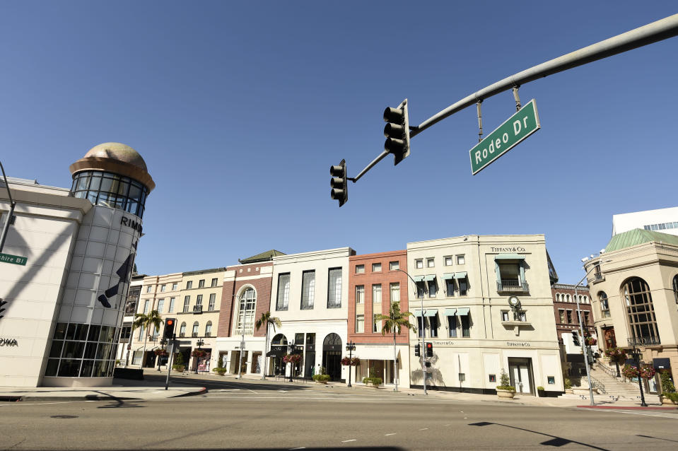 The intersection of Wilshire Boulevard and Rodeo Drive stands free of cars and pedestrians as stay-at-home orders continue in California due to the coronavirus, Monday, March 30, 2020, in Beverly Hills, Calif. (AP Photo/Chris Pizzello)