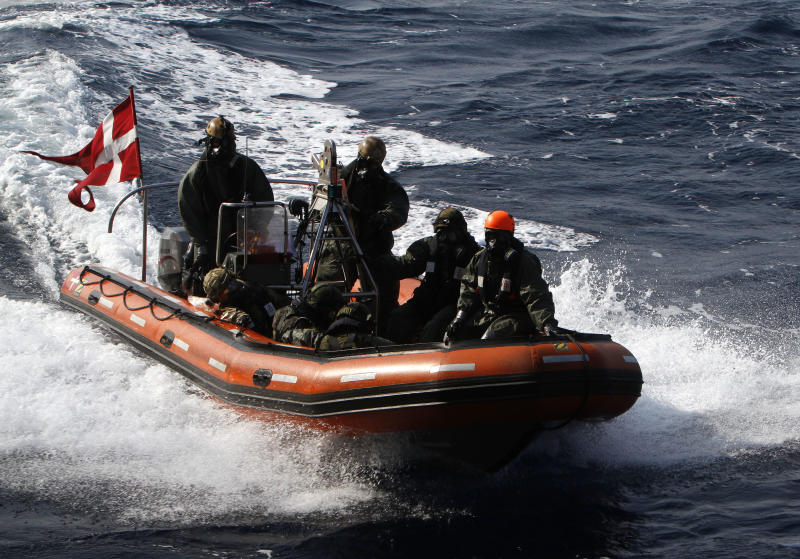 Finnish crew members of the quick response force and Danish personnel conduct a drill on a boat, wearing a protective mask and special uniforms, as part of the emergency drills on Danish warship Esbern Snare on the sea between Cyprus and Syria, Sunday, Jan. 5, 2014. Two cargo ships and their warship escorts set sail at waters near Syria where they will wait for orders on when they can head to the Syrian port of Latakia to pick up more than 1,000 tons of chemical agents. (AP Photo/Petros Karadjias)