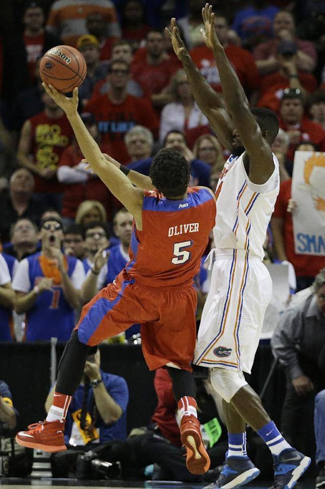 Dayton forward Devin Oliver (5) tries to shoot over Florida center Patric Young (4) during the first half in a regional final game at the NCAA college basketball tournament, Saturday, March 29, 2014, in Memphis, Tenn. (AP Photo/Mark Humphrey)