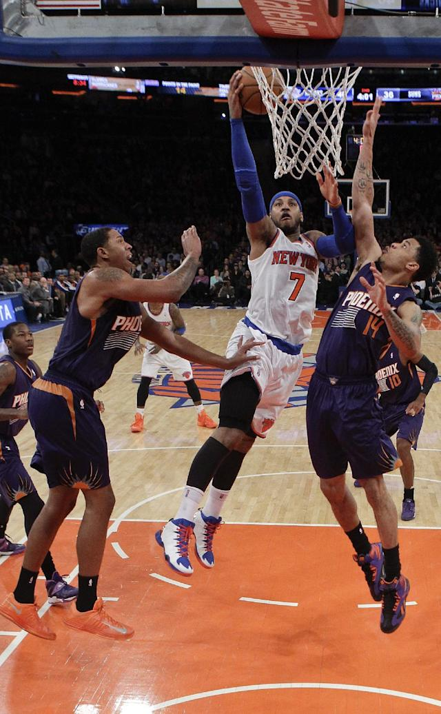 New York Knicks' Carmelo Anthony (7) drives past Phoenix Suns' Gerald Green (14) and Channing Frye (8) during the first half of an NBA basketball game, Monday, Jan. 13, 2014, in New York. (AP Photo/Frank Franklin II)
