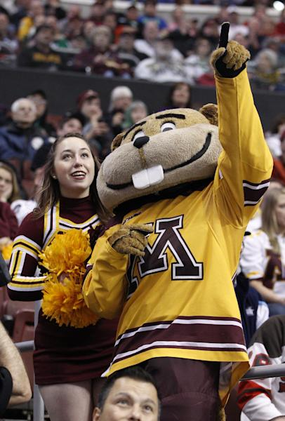 Minnesota's mascot Goldy points things out to one of the cheerleaders during the third period of an NCAA men's college hockey Frozen Four tournament game against North Dakota, Thursday, April 10, 2014, in Philadelphia. Minnesota won 2-1. (AP Photo/Chris Szagola)