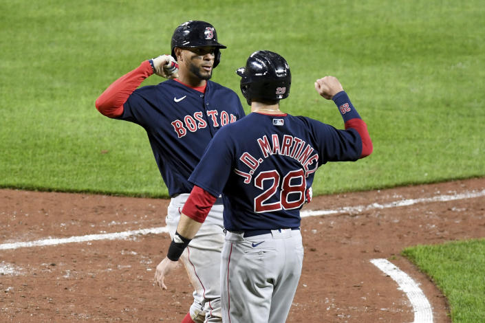Boston Red Sox's Xander Bogaerts celebrates with teammate J.D. Martinez (28) after hitting a two-run home run against the Baltimore Orioles in the sixth inning of a baseball game, Saturday, May 8, 2021, in Baltimore. (AP Photo/Will Newton)