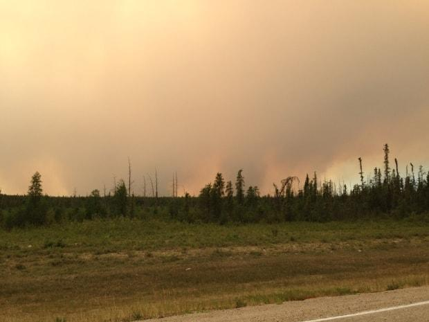 Reddish smoke fills the air near Kakisa, N.W.T. as a 33,000-hectare forest fire burned seven kilometres away from the community in 2014.