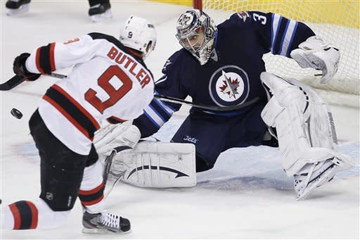 Winnipeg Jets goaltender Ondrej Pavelec (31) saves the shot from New Jersey Devils' Bobby Butler (9) during the first period of an NHL hockey game in Winnipeg, Manitoba, on Thursday, Feb. 28, 2013. (AP Photo/The Canadian Press, John Woods)