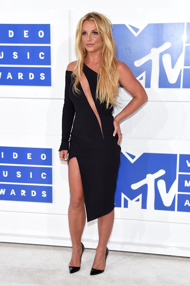 <p>Before her big performance, Britney Spears walked the white carpet in a one-shoulder black dress featuring a sheer diagonal stripe across her chest. <i>(Photo: Getty Images)</i></p>