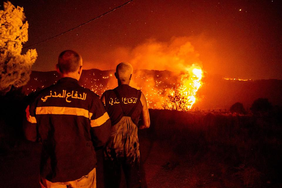 """Civil Defense personnel monitor a wildfire burning through hills in Qobayat, Lebanon on July 28. A Lebanese teenager was killed as he joined volunteers battling to fight the fire.<span class=""""copyright"""">Ethan Swope—Getty Images</span>"""