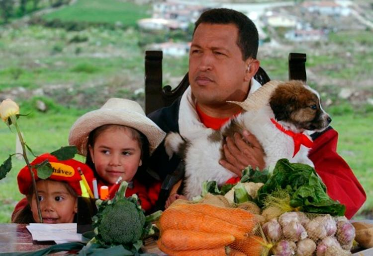 """FILE - In this May 18, 2003 file photo released by Miraflores Press Office, Venezuela's President Hugo Chavez holds a mucuchies pup during his radio and television show """"Hello President"""" in Mucuchies, near Merida, Venezuela. The dog known as mucuchies, or Venezuelan sheepdog, was rescued from near-extinction and historical oblivion by Chavez and is now on its way to being internationally recognized as an official canine breed. (AP Photo/Miraflores Press Office, File)"""