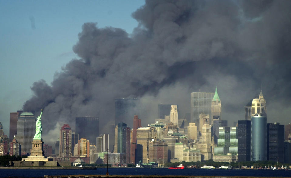 Thick smoke billows into the sky from the area behind the Statue of Liberty, lower left, where the World Trade Center was, on Tuesday, Sept. 11, 2001. (AP Photo/Daniel Hulshizer)