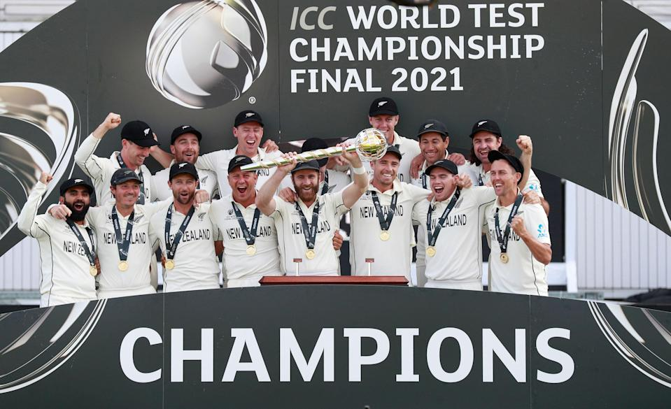 New Zealand players celebrate with the winners trophy after their win in the World Test Championship final cricket match against India, at the Rose Bowl in Southampton.