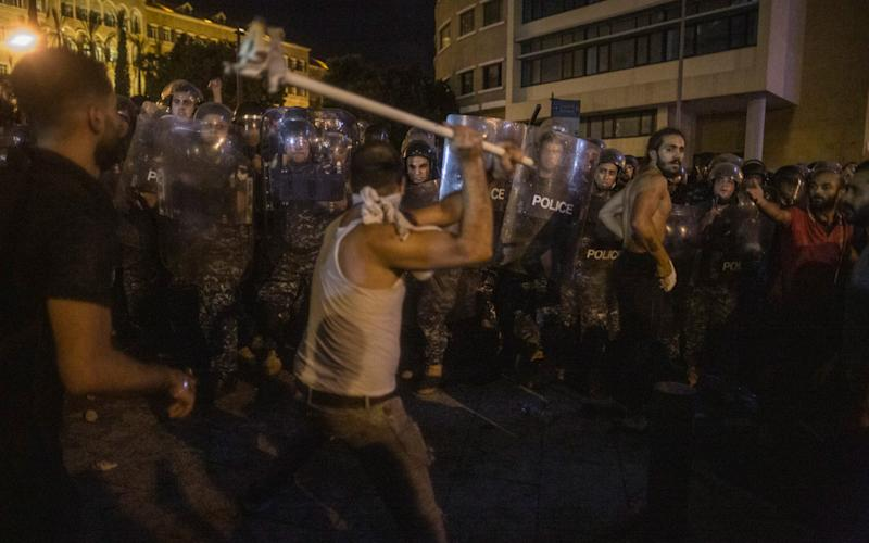 A protester attacks riot police outside the main government offices, the Grand Serail, in Beirut, - Sam Tarling