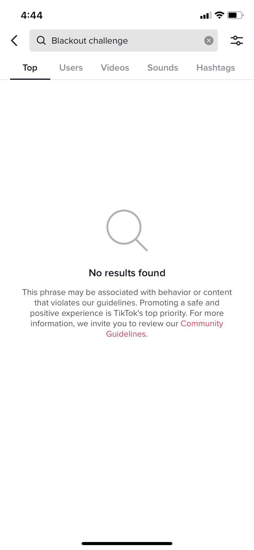 """TikTok's user interface, the text """"Blackout challenge"""" is typed into the search bar. The screen shows no results and a statement that the phrase may be associated with behavior or content that violates tiktok's community guidelines."""
