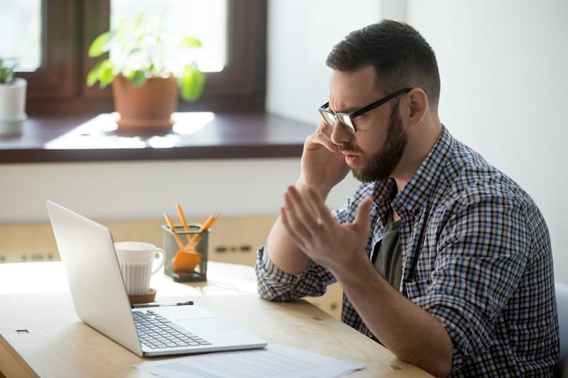 Frustrated man on phone at laptop