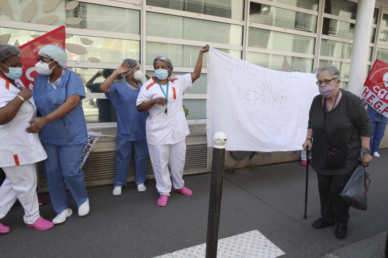 An elderly woman walks past employees demonstrating outside a nursing home of the Korian group, one of the market leaders in the lucrative industry of providing care and assisted living facilities for older adults, Monday, May 25, 2020 in Paris. In France, the group is facing several lawsuits filed by families who have lost loved ones during the coronavirus pandemic that has caused thousands of deaths in French care homes. (AP Photo/Thibault Camus)