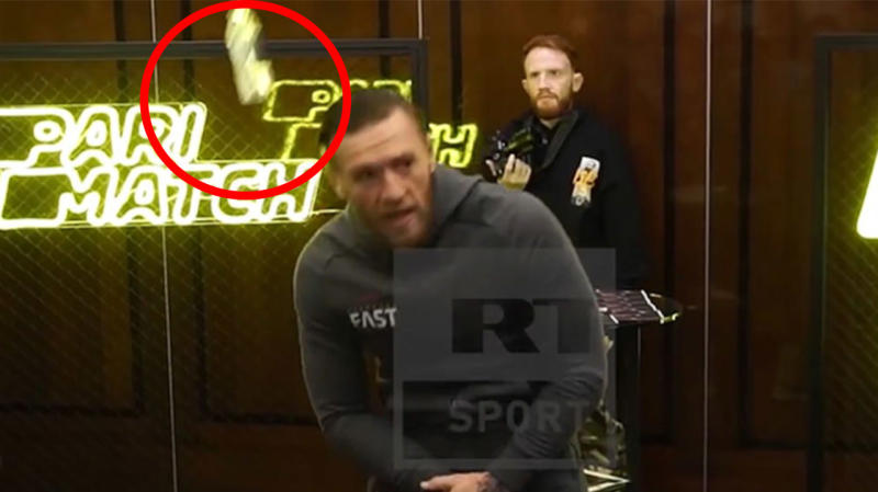 Conor McGregor ducks as a bottle is hurled his way.