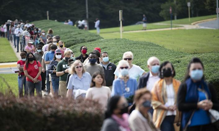 Voters line up to vote during in-person early voting in Fairfax, Virginia on 18 September 2020.