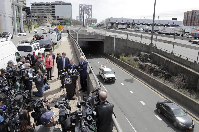 Reporters gather around U.S. Rep. Josh Gottheimer (NJ-5), standing at podium, as he speaks during a news conference near the George Washington Bridge talking about the congressman's plan to fight back against New York City's proposed congestion tax on New Jersey commuters, Wednesday, April 17, 2019, in Fort Lee, N.J. Gottheimer and Rep. Bill Pascrell (NJ-9) announced legislation they say will ensure New Jersey motorists, who already pay up to $15 for bridge or tunnel tolls, won't be charged twice. New York's legislature approved a conceptual plan this month. that will allocate revenue to fix the city's mass transit system. New York would become the first American city to use so-called congestion pricing to reduce gridlock and fund mass transit improvements. (AP Photo/Julio Cortez)