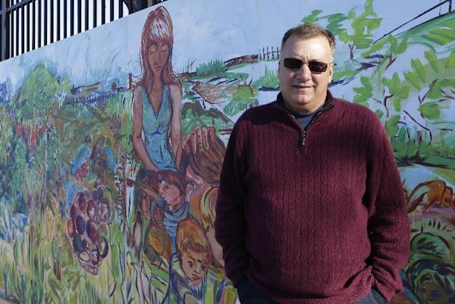 """In this photo taken on Wednesday, Nov. 13, 2013, Secaucus Mayor Michael Gonnelli poses in front of a mural in a park in his town in Secaucus N.J. Northern New Jersey towns hoping to get Super Bowl visitors to spend time and money in the Garden State and not just across the river in Manhattan, realize they need to come up with a creative game plan to separate itself from New York. There's a catch: None of the festivities can employ the words """"Super Bowl,"""" a name that is trademarked by the NFL.(AP Photo/Julio Cortez)"""