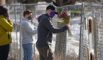 Kiefer Johnson places a bouquet of flowers into a makeshift fence put up around the parking lot outside a King Soopers grocery store where a mass shooting took place a day earlier, in Boulder, Colo., Tuesday, March 23, 2021. (AP Photo/David Zalubowski)