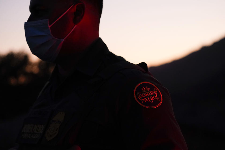 Border Patrol agent Justin Castrejon looks on near a section of new border structure Thursday, Sept. 24, 2020, near Tecate, Calif. President Donald Trump's reshaping of U.S. immigration policy may be most felt in his undoing of asylum. Castrejon says migrants pay $8,000 to $10,000 to be guided through the mountains and picked up by a driver once they reach a road. (AP Photo/Gregory Bull)