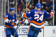 New York Islanders' Mathew Barzal (13) celebrates with teammate Scott Mayfield (24) after scoring a goal during the third period of Game 4 during an NHL hockey second-round playoff series against the Boston Bruins, Saturday, June 5, 2021, in Uniondale, N.Y. (AP Photo/Frank Franklin II)