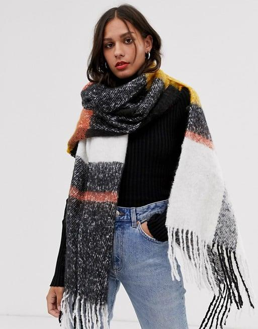 "<p>You'll be cozy wearing this <a href=""https://www.popsugar.com/buy/ASOS-DESIGN-Oversized-Check-Scarf-487254?p_name=ASOS%20DESIGN%20Oversized%20Check%20Scarf&retailer=us.asos.com&pid=487254&price=29&evar1=fab%3Aus&evar9=46575569&evar98=https%3A%2F%2Fwww.popsugar.com%2Fphoto-gallery%2F46575569%2Fimage%2F46576061%2FASOS-DESIGN-Oversized-Check-Scarf&list1=shopping%2Cfall%20fashion%2Caccessories%2Cfall%2C50%20under%20%2450%2Caffordable%20shopping&prop13=api&pdata=1"" rel=""nofollow"" data-shoppable-link=""1"" target=""_blank"" class=""ga-track"" data-ga-category=""Related"" data-ga-label=""https://us.asos.com/asos-design/asos-design-oversized-long-fluffy-blown-up-check-mustard-scarf/prd/11827760?clr=mustard&amp;colourWayId=16398393&amp;SearchQuery=&amp;cid=4174"" data-ga-action=""In-Line Links"">ASOS DESIGN Oversized Check Scarf </a> ($29).</p>"