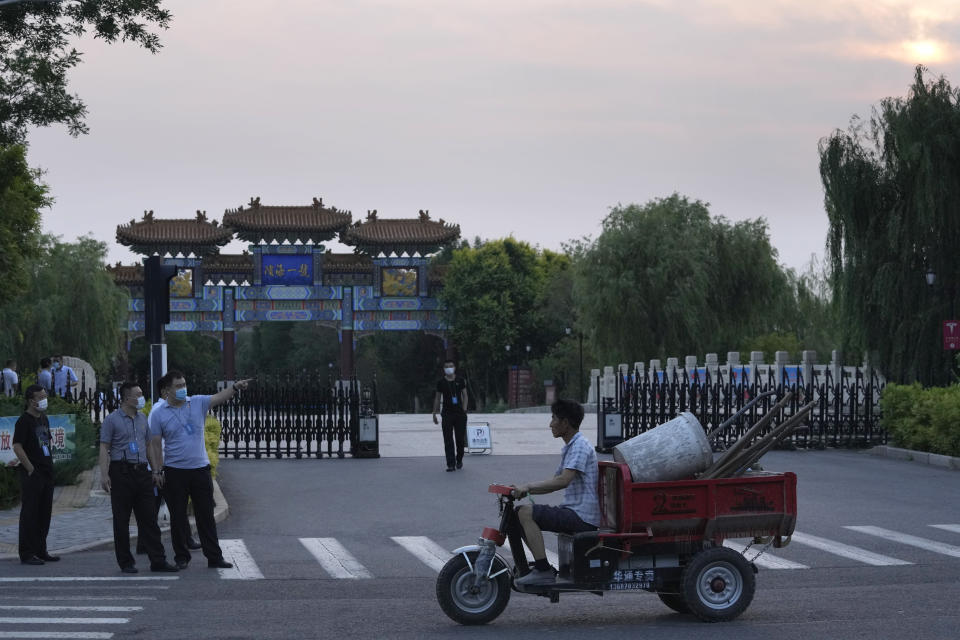 A worker transporting work tools pass by security personnel outside the Tianjin Binhai No. 1 Hotel where U.S. and Chinese officials are expected to hold talks in Tianjin municipality in China on Sunday, July 25, 2021. Deputy Secretary of State Wendy Sherman travelled to China this weekend on a visit that comes as tensions between Washington and Beijing soar on multiple fronts, the State Department said Wednesday. (AP Photo/Ng Han Guan)