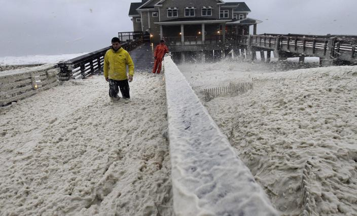 A news crew wades through sea foam blown onto Jeanette's Pier in Nags Head, N.C., Sunday, Oct. 28, 2012 as wind and rain from Hurricane Sandy move into the area.  Governors from North Carolina, where steady rains were whipped by gusting winds Saturday night, to Connecticut declared states of emergency. Delaware ordered mandatory evacuations for coastal communities by 8 p.m. Sunday. (AP Photo/Gerry Broome)