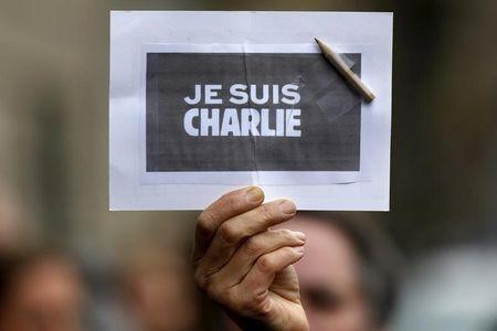 "A person holds a placard with a pencil which reads ""I am Charlie"" during a minute of silence for victims of the shooting at the Paris offices of Charlie Hebdo, in Strasbourg in this January 8, 2015 file picture. REUTERS/Vincent Kessler/Files"