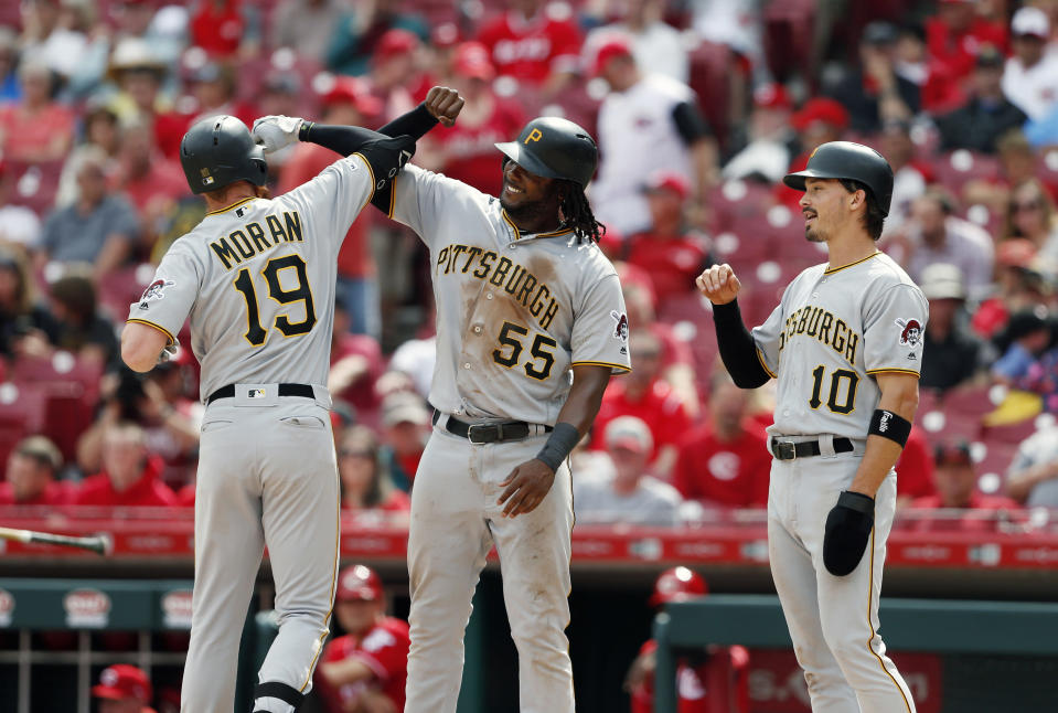 Pittsburgh Pirates' Colin Moran (19) celebrates his three-run home run off Cincinnati Reds starting pitcher Anthony DeSclafani (28) with Josh Bell (55) and Bryan Reynolds (10) during the sixth inning of a baseball game, Wednesday, May 29, 2019, in Cincinnati. (AP Photo/Gary Landers)
