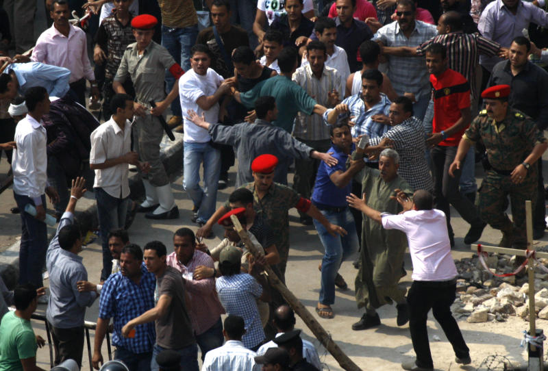 Egyptian Coptic Christians stop a man trying to throw a stone during clashes  in front of the state television building where they protest recent attacks on Christians and churches in Cairo, Egypt, Sunday, May 15, 2011. Egypt's top Christian leader called on his followers Sunday to end a weeklong sit-in in front of a government building on the Nile after a mob attacked the Christian protesters and their supporters, injuring 67. (AP Photo/Khalil Hamra)