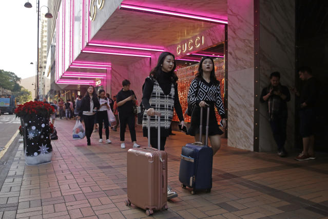 In this Thursday, Nov. 29, 2018 photo, Chinese tourists walk on the Canton Road, the one-stop-shop high street of high-end brands in Hong Kong. The designer boutiques of Manhattan and Paris are feeling the chill of a Chinese economic slowdown that has hammered automakers and other industries. That is jolting brands such as Louis Vuitton and Burberry that increasingly rely on Chinese customers who spend $90 billion a year on jewelry, clothes and other high-end goods. The industry already is facing pressure to keep up as China's big spenders shift to buying more at the spreading networks of luxury outlets in their own country. (AP Photo/Kin Cheung)