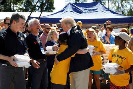 U.S. President Donald Trump embraces a boy while helping hand out meals with North Carolina Governor Roy Cooper (L) at a distribution center at Temple Baptist Church while participating in a tour of Hurricane Florence recovery efforts in New Bern, North Carolina, U.S., September 19, 2018. REUTERS/Kevin Lamarque