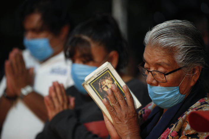 Mourners wearing protective face masks pray during the cross raising ceremony for Luz Maria Gonzalez, in the family home in Valle de Chalco, on the outskirts of Mexico City, Friday, July 3, 2020. Gonzalez, 56, who had long suffered from asthma, diabetes, and hypertension, died two days after her 29-year-old son, who was hospitalized for breathing problems and a cough before dying of complications said to be related to pneumonia and undiagnosed diabetes. (AP Photo/Rebecca Blackwell)