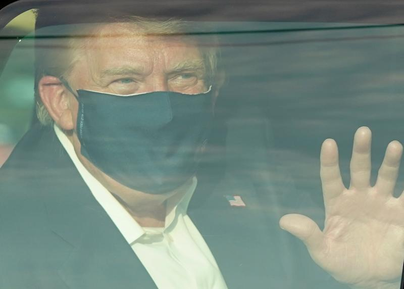 A photo of Donald Trump with a face mask waving to his supporters as he battles coronavirus.