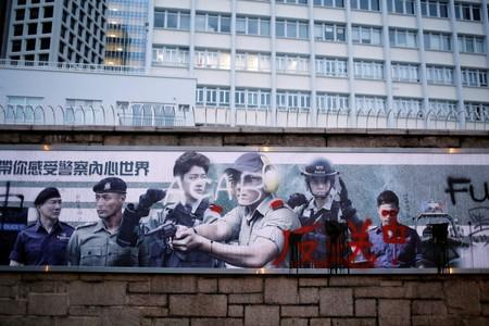 FILE PHOTO: Graffiti against the extradition bill is seen on a Hong Kong Police department banner outside of police headquarters in Hong Kong