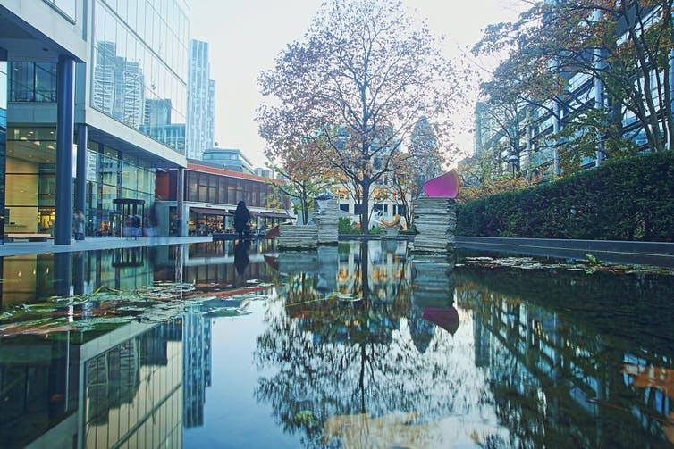 An autumnal tree reflected in a pond adorned with modern sculpture in a regenerated area of London's urban east end.
