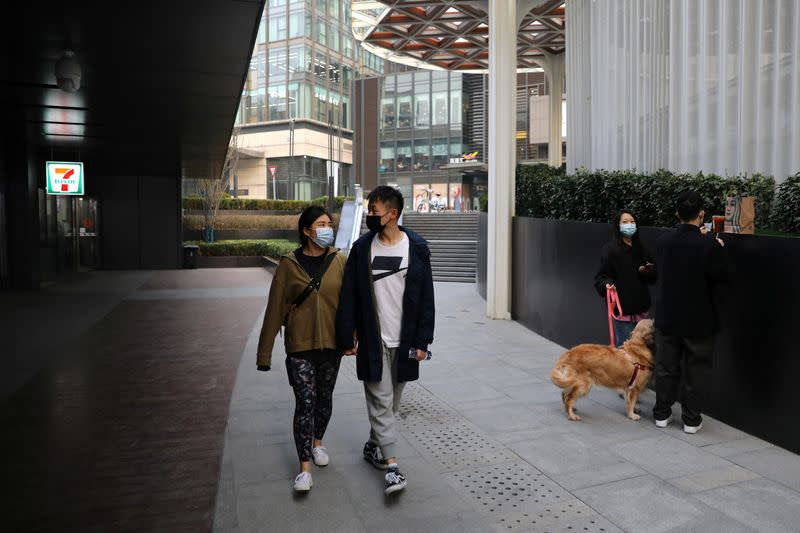 Married couple Liu Zhichang and Yu Tao walk at a plaza after they finished gym class in Beijing