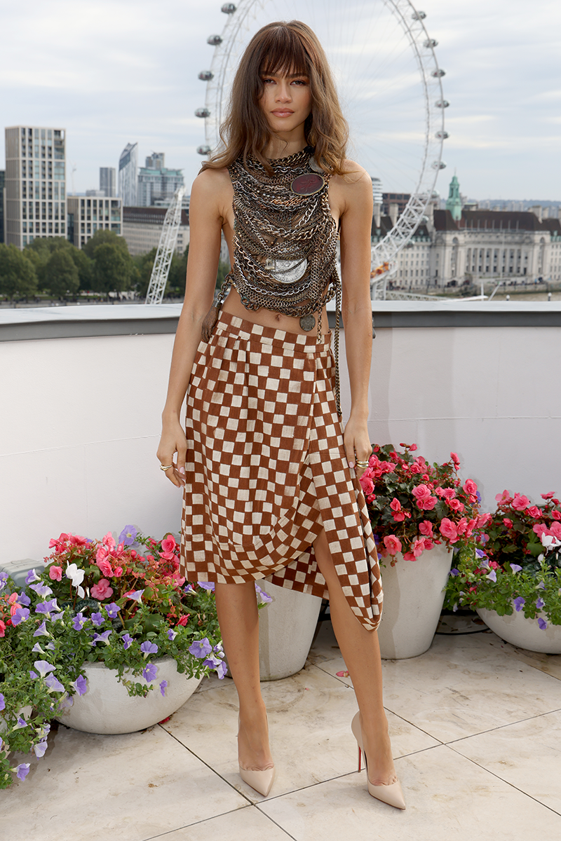 """<p>Zendaya arrived at the Dune London photocall wearing one HELLUVA outfit. The post-apocalyptic feel two-piece set (an appropriate choice, given the film), designed by Vivienne Westwood, features a sleeveless harness which is basically a whole load of layered chains, delicately arranged across the torso and tied at the back. The edgy top is then teamed with a brown and beige checkered knee-length skirt - a fresh-off-the-runway look, according to Law Roach, who shared the catwalk snap on <a href=""""http://instagram.com/p/CVIcSoLsSMi/"""" rel=""""nofollow noopener"""" target=""""_blank"""" data-ylk=""""slk:Instagram"""" class=""""link rapid-noclick-resp"""">Instagram</a>. I mean, c'mon, how fierce does she look?<br></p><p>The star shared pics of her latest look on Instagram with the caption """"When in London…wear <a href=""""https://www.instagram.com/viviennewestwood/"""" rel=""""nofollow noopener"""" target=""""_blank"""" data-ylk=""""slk:@viviennewestwood"""" class=""""link rapid-noclick-resp"""">@viviennewestwood</a>"""" and, like, we couldn't agree more.</p>"""