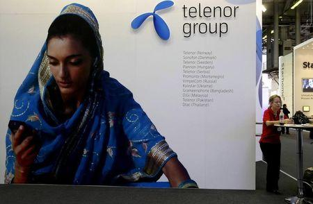 A visitor rests under a Telenor Group sign at the GSMA Mobile World Conference in Barcelona