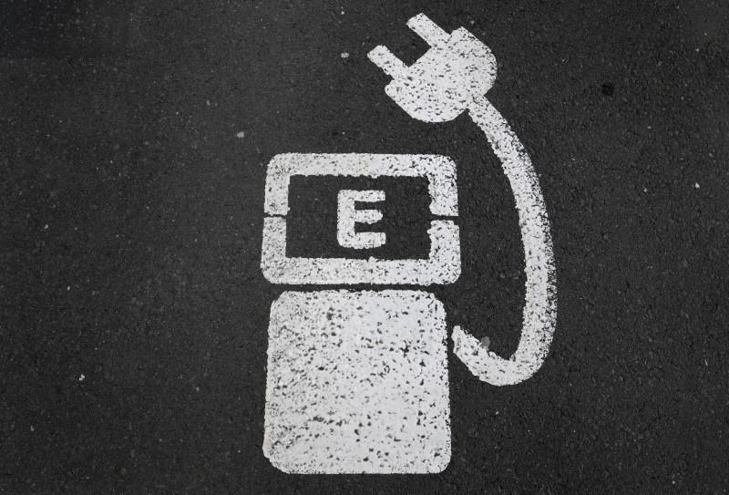 A battery charger sign for electric cars is painted on the ground of a parking ground near the soccer stadium in Wolfsburg