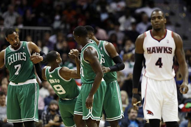 Boston Celtics' Rajon Rondo, second from left, is helped off the floor by teammates Jared Sullinger, left, Brandon Bass and Jeff Green, rear, after being fouled by Atlanta Hawks' Paul Millsap in the third quarter of an NBA basketball game, Wednesday, April 9, 2014, in Atlanta. The Hawks won 105-97. (AP Photo/David Goldman)