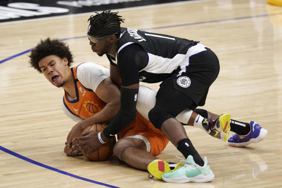 Phoenix Suns forward Cameron Johnson, left, and Los Angeles Clippers guard Reggie Jackson battle for a loose ball during the second half in Game 3 of the NBA basketball Western Conference Finals Thursday, June 24, 2021, in Los Angeles. (AP Photo/Mark J. Terrill)