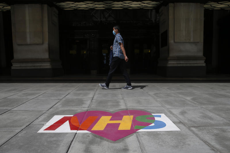 """LONDON, ENGLAND - JUNE 14: A man wearing a mask walk past a NHS sign on the footpath outside of Selfridges on Oxford street on June 14, 2020 in London, England. Many """"non-essential"""" shops are allowed to reopen from June 15 after being closed for more than two months due to risks posed by Covid-19. (Photo by Hollie Adams/Getty Images)"""