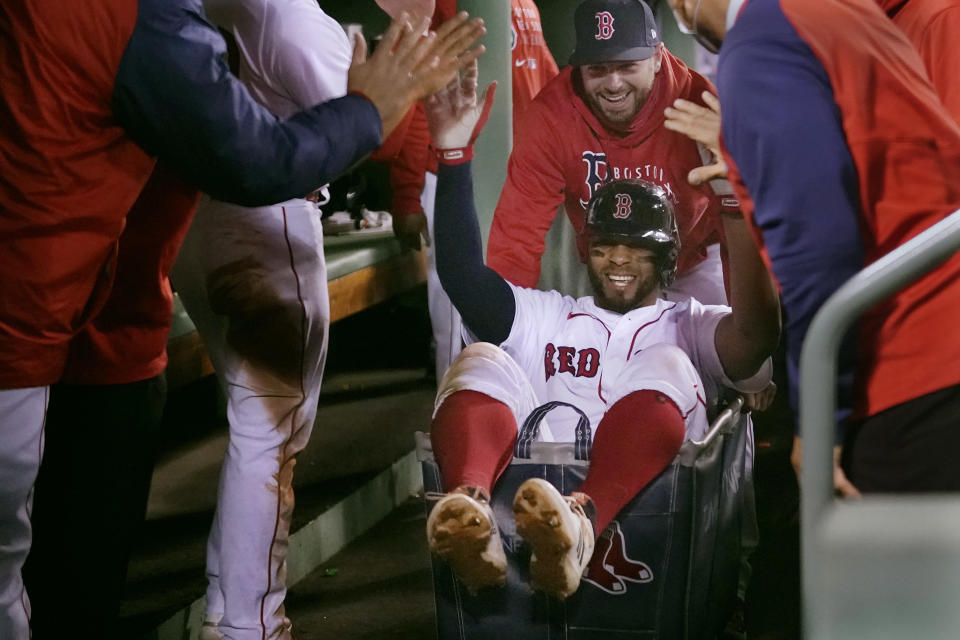 Boston Red Sox's Xander Bogaerts high-fives teammates while being pushed in a laundry cart through the dugout after his two-run home run against the Detroit Tigers during the second inning of a baseball game at Fenway Park, Tuesday, May 4, 2021, in Boston. (AP Photo/Charles Krupa)